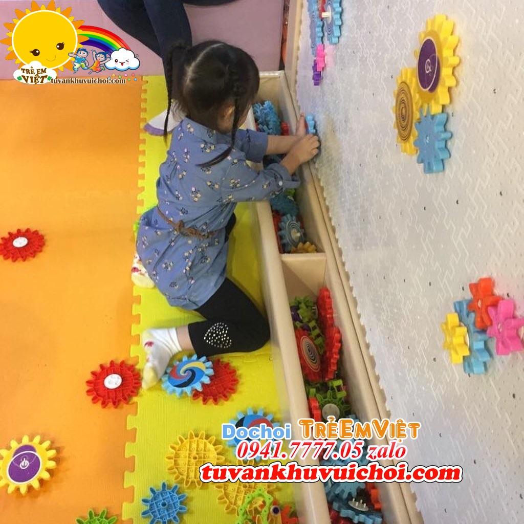 Bé lắp ghép các miếng lego tường.